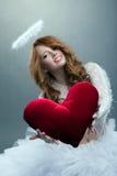Muchacha linda en el traje del ángel que presenta con el corazón del peluche Imagen de archivo