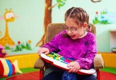 Muchacha linda en la silla de ruedas que juega con el juguete que se convierte en la guardería para los niños con necesidades esp foto de archivo