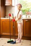 Muchacha linda en los guantes de goma que barren el piso en la cocina con la esponja Foto de archivo libre de regalías