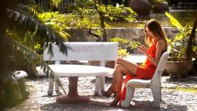 Muchacha linda en mensaje de textos rojo en el teléfono en jardín almacen de metraje de vídeo