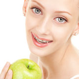 Muchacha linda en paréntesis con la manzana en el fondo blanco Fotografía de archivo libre de regalías