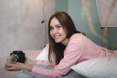 Muchacha linda en pijamas rosados en la cama Imagen de archivo