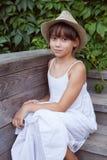 Muchacha linda en un sombrero que se sienta en el pórtico Foto de archivo libre de regalías