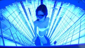 Muchacha linda en un traje de baño en una cabina especial con las lámparas ULTRAVIOLETA para el tratamiento del psoriasis almacen de video