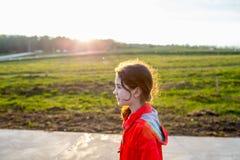Muchacha linda en una capa roja en el fondo verde del campo Imagen de archivo