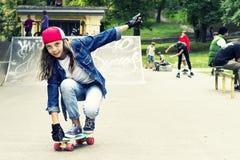 Muchacha linda en una gorra de béisbol con un monopatín en un parque del patín deportes Foto de archivo