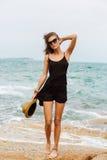 Muchacha linda en vestido negro del verano en las piedras grandes Imágenes de archivo libres de regalías