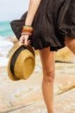 Muchacha linda en vestido negro del verano en las piedras grandes Foto de archivo libre de regalías