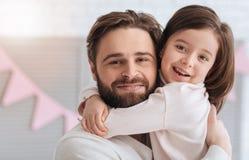 Muchacha linda encantada que abraza a su papá Fotografía de archivo libre de regalías