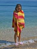 Muchacha linda envuelta en la toalla que se coloca en el mar Fotos de archivo