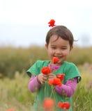 Muchacha linda feliz del niño en campo de las amapolas Niños felices Fotos de archivo libres de regalías