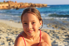 Muchacha linda feliz del preadolescente que se sienta y que sonríe en la costa de caliente Fotos de archivo libres de regalías
