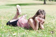 Muchacha linda feliz que pone en un campo de hierba Imagen de archivo