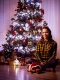Muchacha linda feliz que se sienta con el pequeño perrito en un cuarto hermoso con un árbol de navidad Imagen de archivo libre de regalías