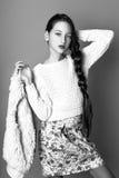 Muchacha linda hermosa de la moda adolescente en un suéter y una falda con el pelo largo que presenta en estudio Foto blanco y ne Fotos de archivo libres de regalías