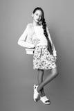 Muchacha linda hermosa de la moda adolescente en un suéter y una falda con el pelo largo que presenta en estudio Foto blanco y ne Fotografía de archivo
