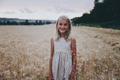 Muchacha linda hermosa en un campo de trigo Imagen de archivo