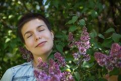Muchacha linda hermosa senjoying día caliente debajo de árboles florecientes de la lila fotografía de archivo
