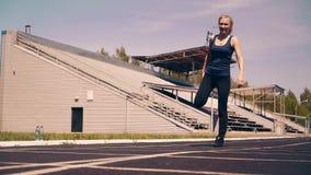 Muchacha linda joven, constitución deportiva, en el estadio Ella hace el calentamiento, antes de entrenar metrajes