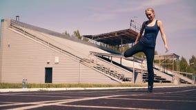 Muchacha linda joven, constitución deportiva, en el estadio Ella hace el calentamiento de los músculos, antes de entrenar metrajes