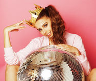 Muchacha linda joven del disco en fondo rosado con la bola de discoteca y la corona Fotografía de archivo
