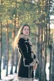 Muchacha linda joven del retrato que presenta en el bosque en la puesta del sol Fotografía de archivo
