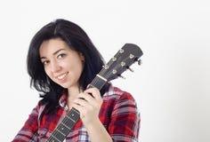 Muchacha linda joven en una camisa a cuadros que celebra una guitarra acústica y una sonrisa Imagenes de archivo
