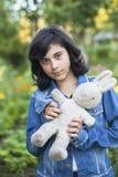 Muchacha linda joven en una chaqueta del dril de algodón con un juguete viejo Imágenes de archivo libres de regalías