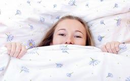 Muchacha linda joven que descansa sobre cama Foto de archivo libre de regalías