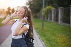 Muchacha linda joven que disfruta de música con los auriculares al aire libre Imágenes de archivo libres de regalías