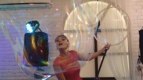 Muchacha linda joven que juega con las burbujas de jabón grandes, haciendo la demostración, primer metrajes