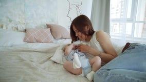 Muchacha linda joven que juega con su hijo en la cama Una madre joven está jugando con un bebé en la cama almacen de video