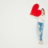 Muchacha linda joven que lleva a cabo el corazón rojo para el día de tarjeta del día de San Valentín Fotos de archivo