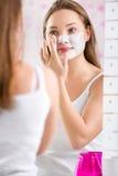 Muchacha linda joven que pone la máscara facial en su cara Imágenes de archivo libres de regalías