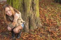 Muchacha linda joven que se sienta en el bosque o el parque del otoño Imagen de archivo
