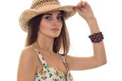 Muchacha linda joven que sostiene el sombrero de la mano en su cabeza y miradas en el primer de la cámara Fotografía de archivo