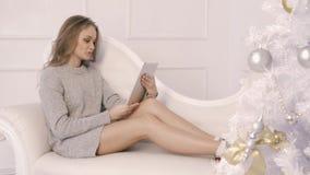 Muchacha linda joven que usa una tableta que se sienta en un sofá metrajes