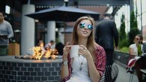 Muchacha linda joven satisfecha que se sienta en el café de la calle y el té de consumición almacen de metraje de vídeo