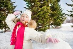 Muchacha linda lista para lanzar la bola de nieve durante día Fotografía de archivo libre de regalías