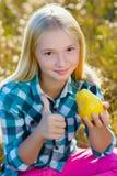 Muchacha linda o pera sana y jugosa comida adolescente al aire libre Foto de archivo