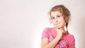 Muchacha linda ocho años con el pelo rizado en fondo gris imágenes de archivo libres de regalías