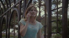Muchacha linda ocupada con el teléfono móvil que camina al aire libre almacen de video