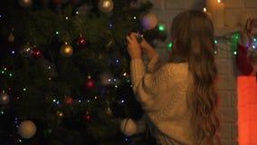 Muchacha linda que adorna el árbol de navidad que se prepara para la víspera del día de fiesta, tradiciones de la familia almacen de video