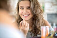Muchacha linda que aplica lustre del labio Imagen de archivo libre de regalías