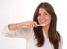 Muchacha linda que aplica sus dientes con brocha Foto de archivo libre de regalías