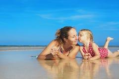 Muchacha linda que besa a la madre sonriente feliz en la playa del mar Imagen de archivo