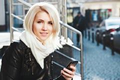 Muchacha linda que celebra el teléfono móvil y la sonrisa Fotos de archivo