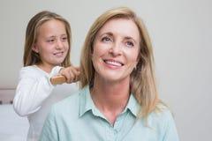 Muchacha linda que cepilla su pelo de las madres Imagen de archivo
