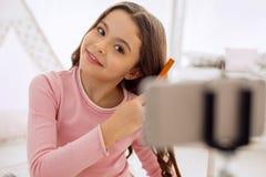 Muchacha linda que cepilla su pelo mientras que filma tutorial Fotos de archivo