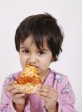 Muchacha linda que come la rebanada de la pizza Imagen de archivo